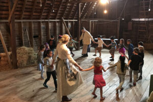 Children and teachers dancing in a circle during Spring on the Farm HATS Class at Stuhr Museum.
